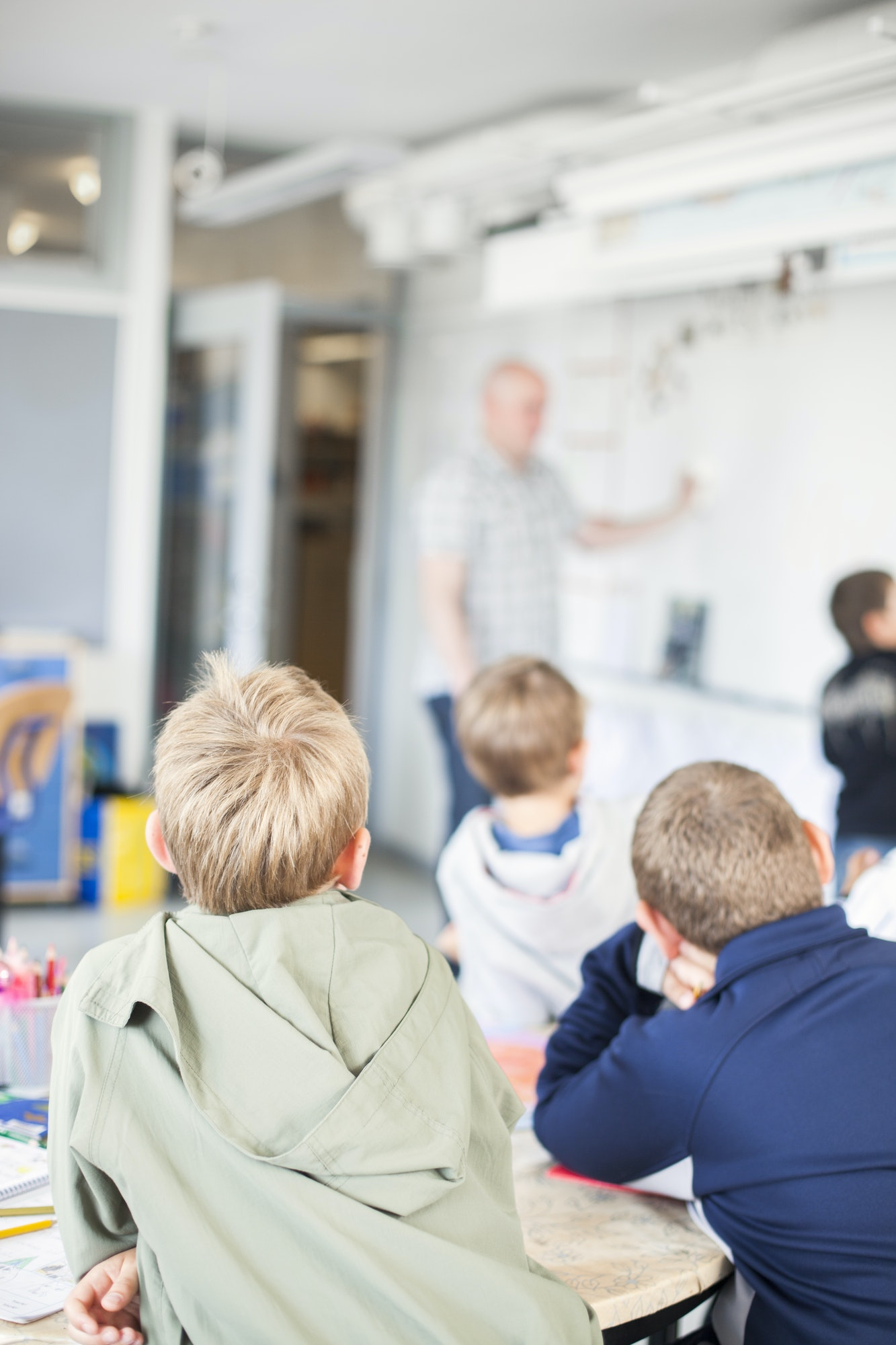 Children looking at teacher during lecture in classroom