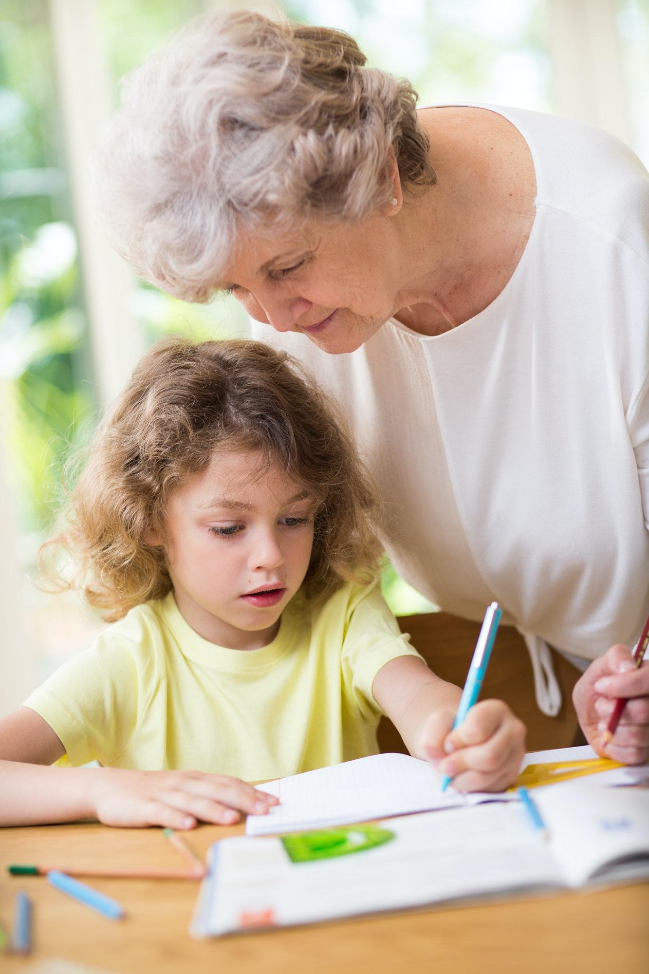 Grey grandmother and her cute grandson do homework